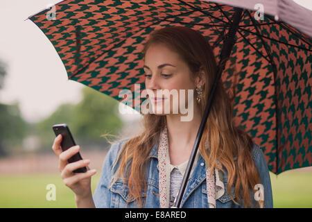 Jeune femme avec parapluie texting on smartphone in park Banque D'Images