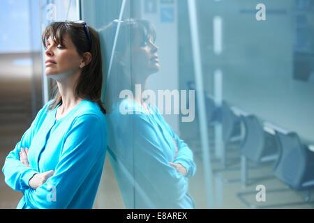 Mature businesswoman leaning against glass wall in office avec les yeux fermé Banque D'Images
