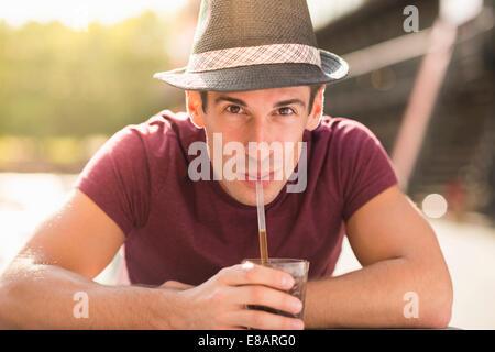 Jeune homme portant un chapeau de paille à boire Banque D'Images