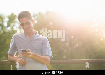 Young man using cell phone Banque D'Images