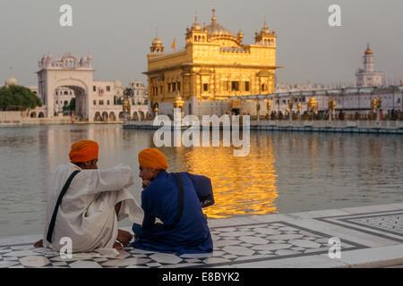 Deux jeunes hommes assis en face du Harmandir Sahib, ou Temple d'Or, l'un des sites les plus vénérés pour les Sikhs, Banque D'Images