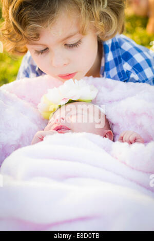 Jeune garçon mignon à regarder sa Sœur bébé fille nouveau-né. Banque D'Images
