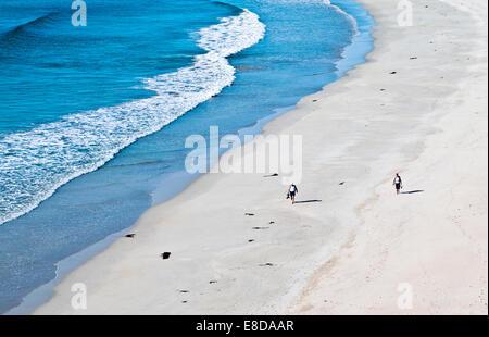 Couple marchant pieds nus le long d'une belle plage de sable au bord de l'eau, chaud soleil d'été, Balnakeil Bay Banque D'Images