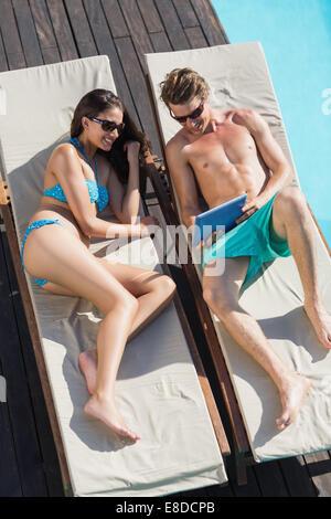 Couple sur les chaises longues au bord de piscine Banque D'Images