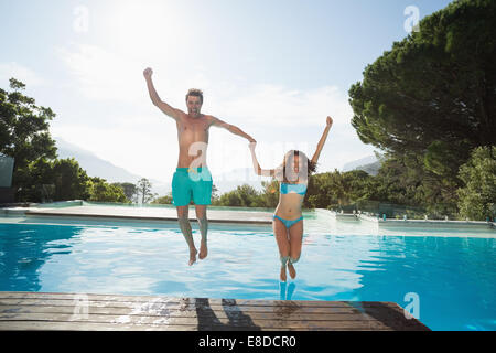 Cheerful young couple jumping into swimming pool Banque D'Images