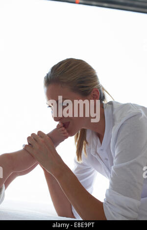 Mère embrassant les pieds de son bébé Banque D'Images