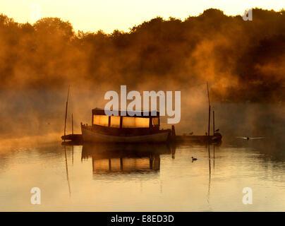 Peterborough (Cambridgeshire, Angleterre. 5 octobre, 2014. Un bateau est éclairé comme brume matinale plane sur Banque D'Images