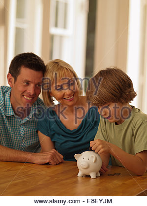 Parents fils mettait pièce dans piggy bank Banque D'Images