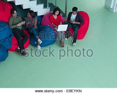 Les gens d'affaires dans des sièges-sacs looking at laptop Banque D'Images