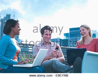 Smiling man et les femmes à l'aide d'ordinateurs portables sur balcon urbain Banque D'Images