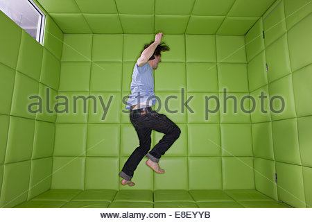 Man dancing in padded room Banque D'Images