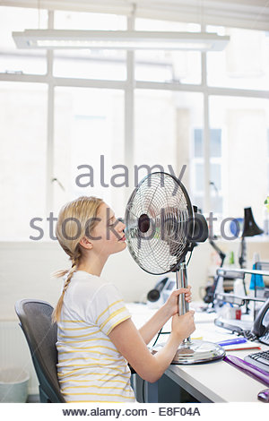 Smiling woman sitting in front of fan in office Banque D'Images