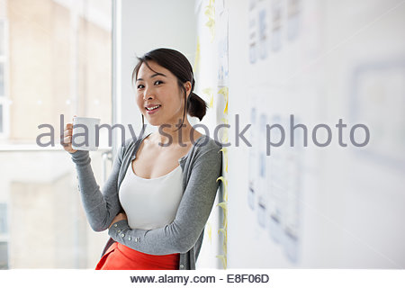 Smiling businesswoman leaning against tableau blanc et boire du café Banque D'Images
