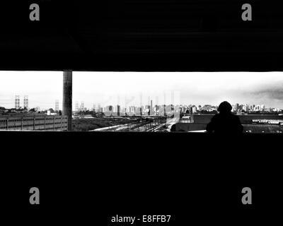 Silhouette d'une personne à la recherche à l'horizon de la ville, São Paulo, Brésil