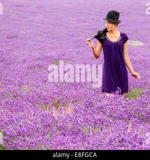 Femme avec chapeau et parapluie debout dans champ de lavande Banque D'Images