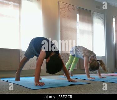 Deux enfants faisant bas yoga pose Banque D'Images