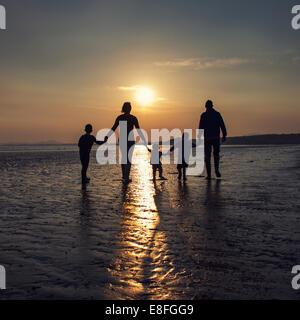 Silhouette d'une famille sur la plage holding hands Banque D'Images