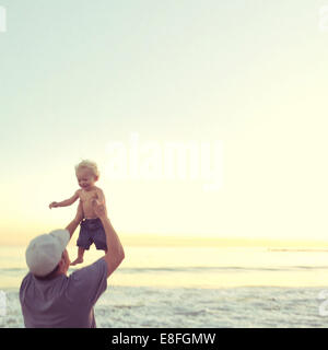 Père levant son fils de bébé dans l'air à la plage, Californie, États-Unis Banque D'Images
