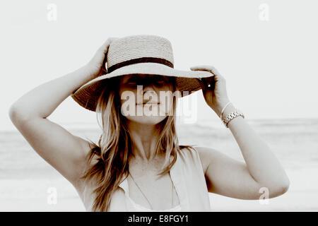 Portrait d'une femme souriante debout sur la plage tenant son chapeau, Afrique du Sud Banque D'Images