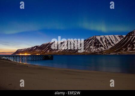 Lumières du nord sur Westfjords avec la ville de Flateyri au loin, l'Islande