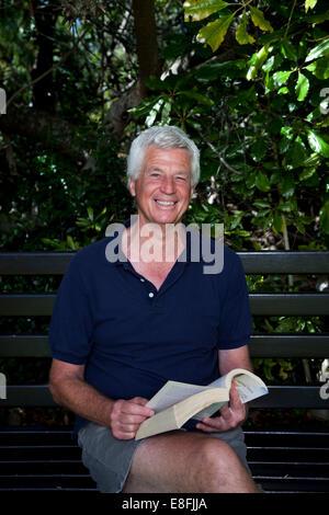 Senior man sitting on livre avec banc de jardin Banque D'Images