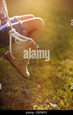 Gros plan sur les jambes d'une fille assise sur une balançoire de corde dans le jardin, Mississippi, États-Unis