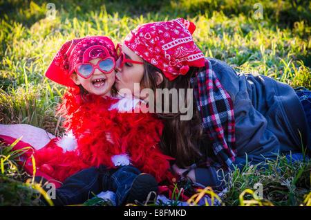 Femme assise dans un pré embrassant sa fille, Texas, États-Unis Banque D'Images