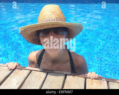 Smiling woman in swimming pool, wearing straw hat Banque D'Images