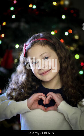 Girl making heart shape with hands in front of Christmas Tree Banque D'Images