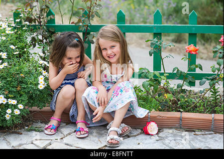 Deux jeunes filles (4-5) assis à l'extérieur et de rire Banque D'Images