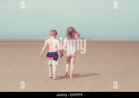 Girl and boy holding hands on beach Banque D'Images
