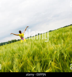 Vue arrière de la femme en champ avec les bras tendus