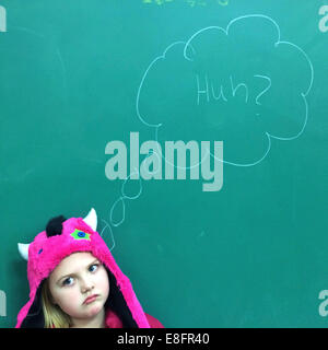 Portrait of a Girl standing in front of blackboard avec expression perplexe