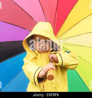 Garçon dans un imperméable tenant un parapluie multi-couleur Banque D'Images