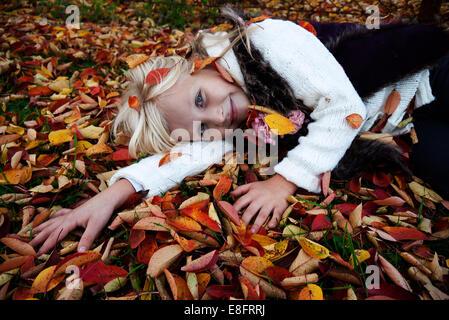 Fille souriante couché sur l'herbe parmi les feuilles d'automne