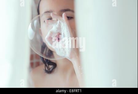 Fille debout dans la douche bulles de savon Banque D'Images