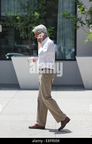 Vue latérale du businessman walking down street alors que talking on mobile phone Banque D'Images