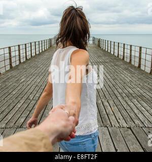 UK, femme holing la main de l'homme sur la jetée