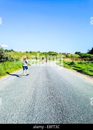 Vue arrière de l'homme couler sur route avec deux fils, Danemark Banque D'Images