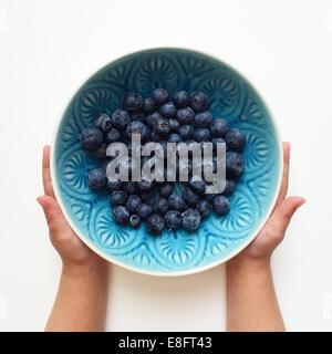 Boy holding un bol de bleuets Banque D'Images