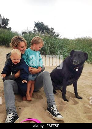 Portrait d'une mère assis sur la plage avec deux fils et le chien Banque D'Images