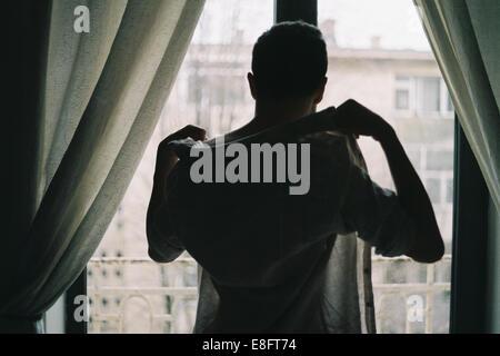Homme debout devant une fenêtre s'habille