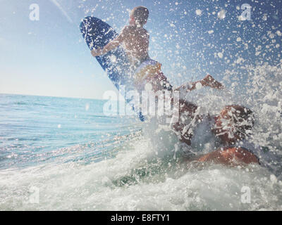 Père et fils jouant dans l'océan avec planche de surf, Californie, États-Unis