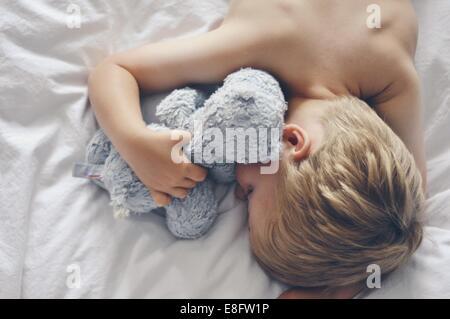 Vue de dessus le garçon endormi dans le lit avec ours Banque D'Images