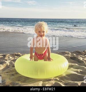 Garçon debout dans un anneau en caoutchouc gonflables sur Beach, Californie, Amérique, USA Banque D'Images