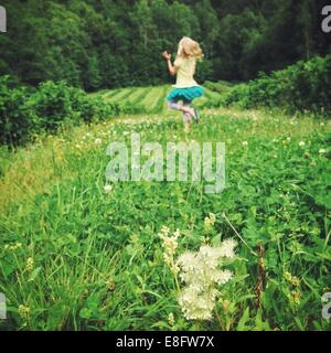 Girl (12-13) jumping on meadow Banque D'Images