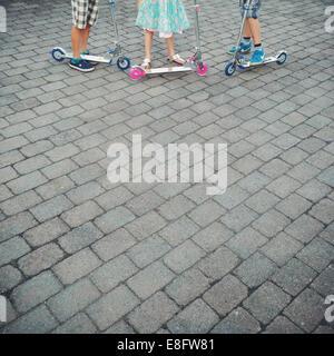 Gros plan de trois enfants debout avec leurs scooters de poussée