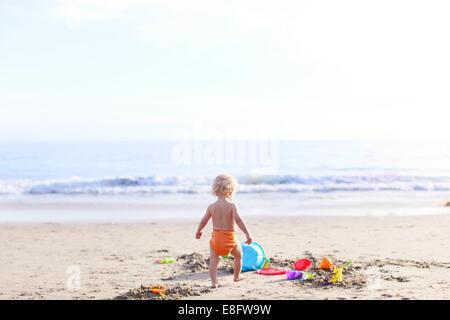 Vue arrière du garçon jouant sur la plage Banque D'Images
