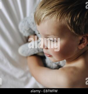 Close up of boy lying in bed with stuffed toy Banque D'Images