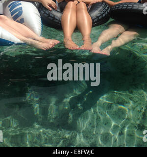 Trois femmes assises dans des anneaux gonflables en caoutchouc dans une piscine Banque D'Images